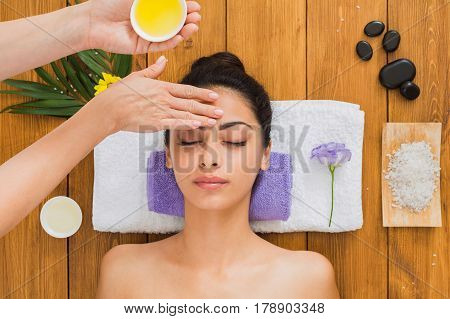 Indian aroma spa wellness center. Professional face lifting lemon massage to beautiful girl in cosmetology cabinet or beauty parlor.