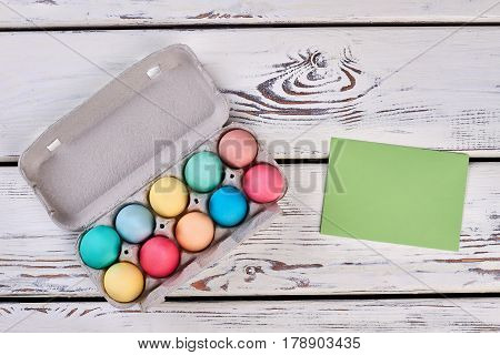 Easter egg tray, blank card. Green paper on white wood.