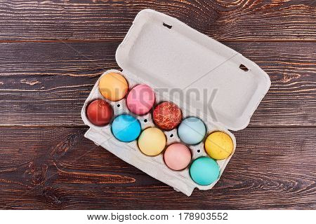 Egg tray on brown wood. Top view of Easter eggs.