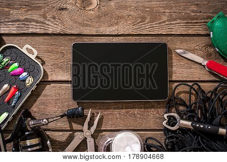 Fishing tackle - fishing spinning, fishing line, hooks and lures on wooden background. Top view. Copy space. Still life