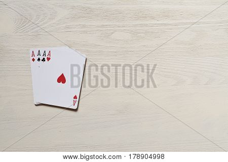 four aces. on a light wooden table. Playing cards, casino. Risk and luck abstraction. Free space for your text.