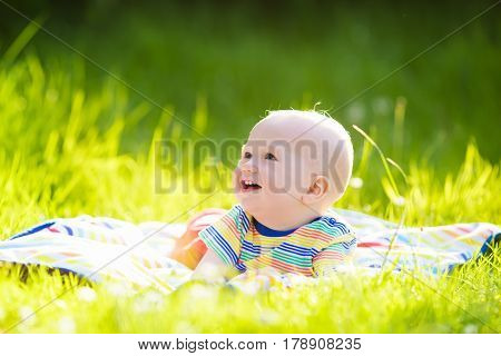 Baby Boy With Apple On Family Garden Picnic