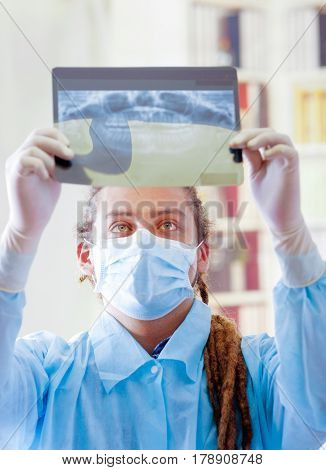 Young doctor with long dread locks posing for camera, holding up x ray image staring at it, wearing facial mask, clinic in background, medical concept.