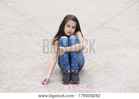 Sad girl sitting on the ground in a circle