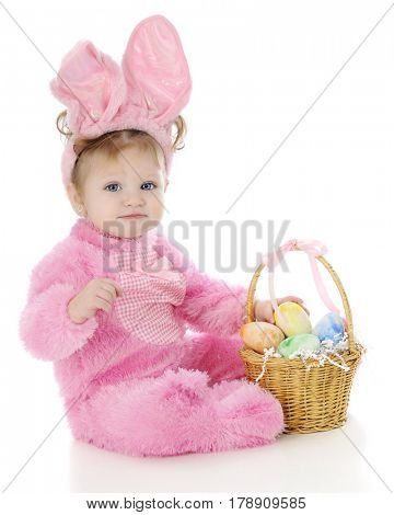 An adorable baby girl sitting as an Easter Bunny with a small basket full of colorful eggs.  On a white background.