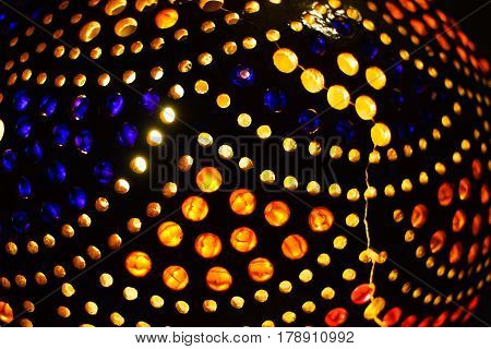 Detail Of Indian Lamp With Lots Of Colorful Yellow Red And Blue Dots With Light In The Dark