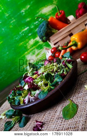 Provence mix salad. Leaves of endive or chicory, lamb and rose salad. Raw vegetables. On wooden table.