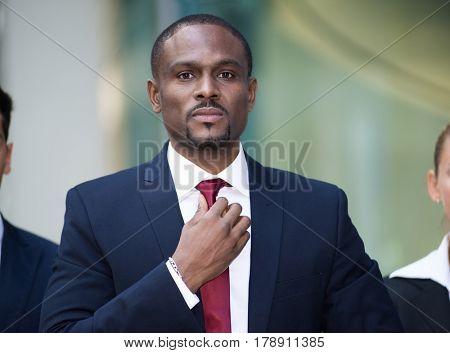 Handsome employee adjusting his necktie