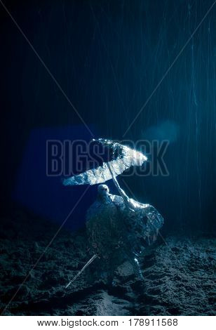 Dark Creepy Composition Of A Man Figure Made Of Aluminium Paper With Sword And Umbrella During Hard