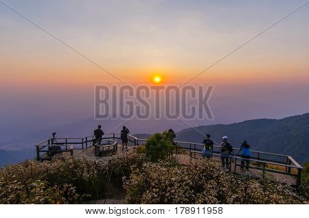 photographer group taking picture of landscape during sunset at top of mountain, with grain, image contain certain grain or noise and soft focus.