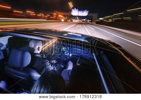 driving at night on a highway with people in the car, seen through the glass roof