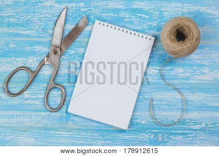 Vintage scissors notebook and rope on a wooden table. The concept of training surprise.