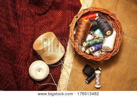 Cotton Threads For Sewing And Needles In A Woven Basket On A Wool Sweater And Leather Cloth, Home Wo