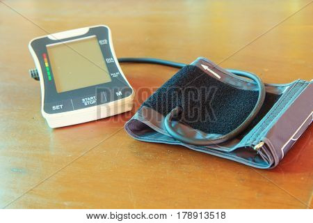 The digital sphygmomanometer on the wood table