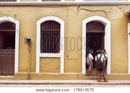PANJIM, INDIA - FEB 25, 2017: Schoolgirls talking in front of old school building in historical indian town on February 25, 2017. Near 5 million tourists visit Goa annually