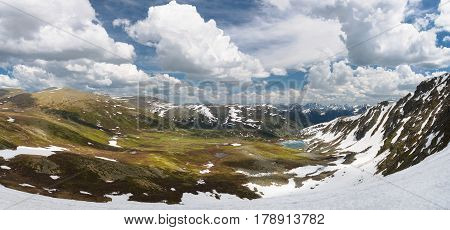 panorama of a picturesque mountain view with small lake and snow made in Altay mountains