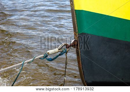Close up of yellow green black boat tied at the coast in Baltic Sea. Moorage