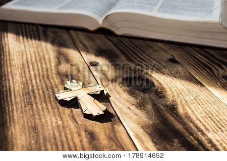 a christian cross and bible on wooden background