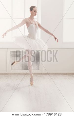 Classical Ballet dancer side view. Beautiful graceful ballerina practice ballet positions in tutu skirt near large window in white light hall. Ballet class training, high-key soft toning.