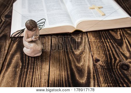 an angel and bible on wooden background