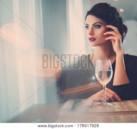 Elegant lady with glass of wine alone in restaurant