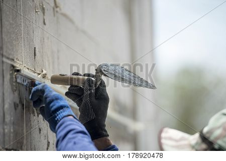 hand of worker plastering cement wall in construction site