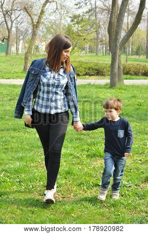 Happy mom and son play in the park in spring. Mother have quality time with her boy at the park