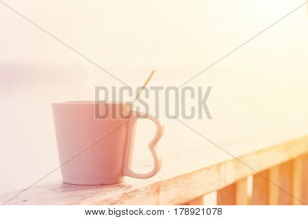 Morning cup of coffee or hot drink at sunrise warm tone