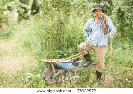 Smiling farmer with garden tools, wheelbarrow and rope standing in his garden