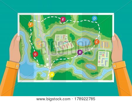 Folded paper city suburban map in hands. Abstract generic map with roads, buildings, parks, river, lake. GPS and navigation. Vector illustration in flat style