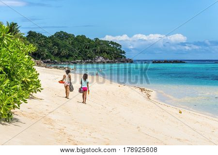 Anse Royale Mahe Island Seychelles - December 152015: People walking in the sand in Spectacular Anse Royale beach and in the background some people enjoying the Anse Royale Beach Mahe Island Seychelles.