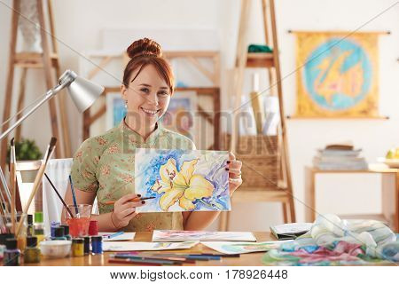Female painter showing flower she has just drawn