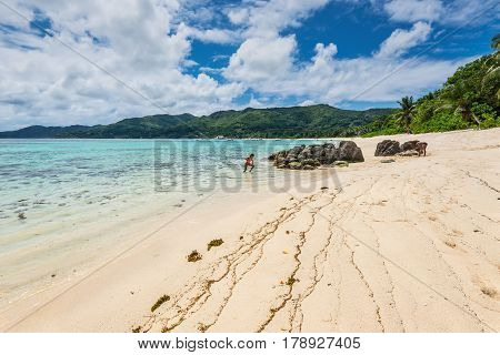 Anse Royale Mahe Island Seychelles - December 15 2015: Spectacular Anse Royale beach and in the background some people enjoying the Anse Royale Beach Mahe Island Seychelles.