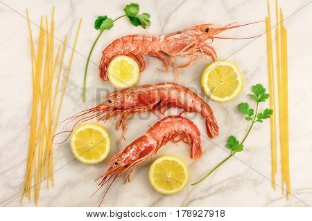 Raw shrimps with slices of lemon, cilantro sprigs, and spaghetti pasta, shot from above on a white marble table