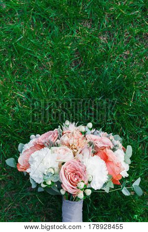 Wedding background vertical. Bouquet from rose flowers on grass. Bridal floral decoration detail outdoors in summer park, copy space