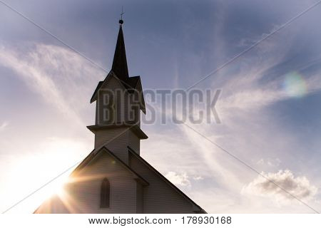 Top of church and steeple with sunburst behind and feathery clouds.