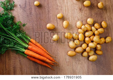 Potatoes with carrot. Raw new potato. Fresh natural vegetables. Organic food on wooden background.