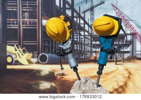 Two electric jackhammers and a helmet stick out of a concrete block against the background of a construction poster.