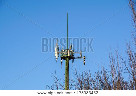 Steel telecommunication tower with antennas over blue sky and trees .