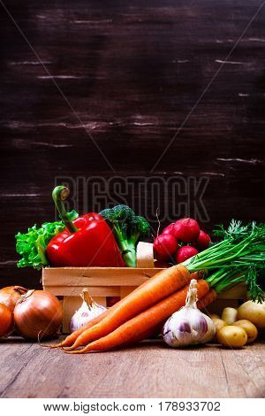 Vegetables. Potatoes, carrot and red pepper. Lettuce salad, garlic and brocoli. Onion and radish. Wooden basket on rustic table.