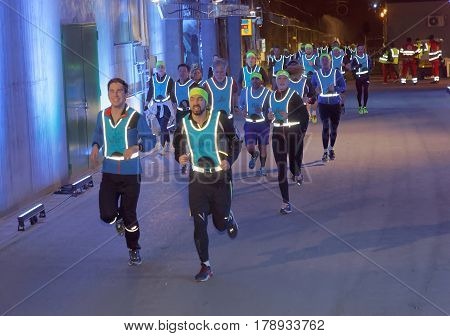 STOCKHOLM SWEDEN - MAR 25 2017: Group of runners in blue reflex vest in a tunnel with blue light in the Stockholm Tunnel Run Citybanan 2017. March 25 2017 in Stockholm Sweden