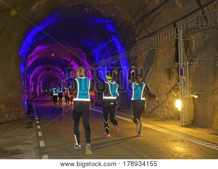 STOCKHOLM SWEDEN - MAR 25 2017: Rear view of a group of runners in blue reflex vest in a tunnel with blue light in the Stockholm Tunnel Run Citybanan 2017. March 25 2017 in Stockholm Sweden