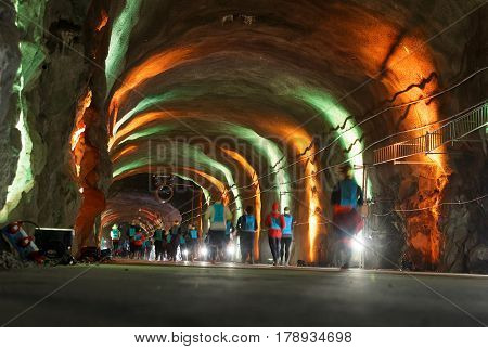 STOCKHOLM SWEDEN - MAR 25 2017: Group of runners in a tunnel with green and orange light in the Stockholm Tunnel Run Citybanan 2017. March 25 2017 in Stockholm Sweden