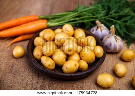 Potatoes in plate. Carrot, garlic and raw new potato. Fresh natural vegetables. Organic bio food on rustic wooden table.