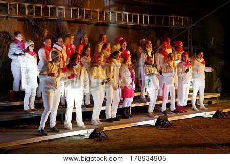 STOCKHOLM SWEDEN - MAR 25 2017: Choir in white and red dresses in a tunnel in the Stockholm Tunnel Run Citybanan 2017. March 25 2017 in Stockholm Sweden