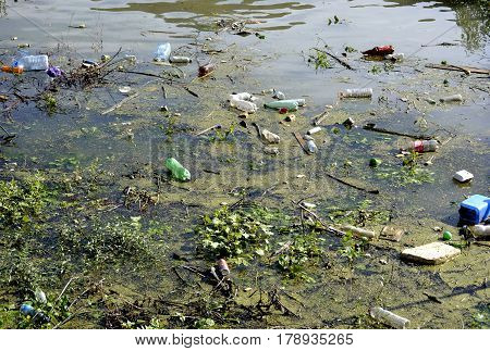 river water polluted by various, organic and inorganic trash