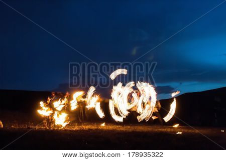 Amazing Impressive Freeze light fire show with fire trails highly in mountains with a colorful blue sky