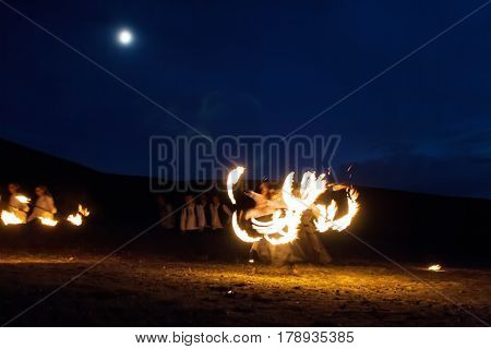 Amazing Impressive Freeze light fire show with fire trails highly in mountains with a moon in a colorful blue sky