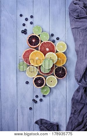 Variety of citrus fruits (orange blood oranges lemons grapefruits and limes) with blueberries with grey fabric over a blue rustic wood table top. Image shot from overhead.