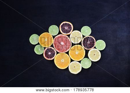 Variety of citrus fruits (orange blood oranges lemons grapefruits and limes) over a black rustic background. Image shot from overhead.